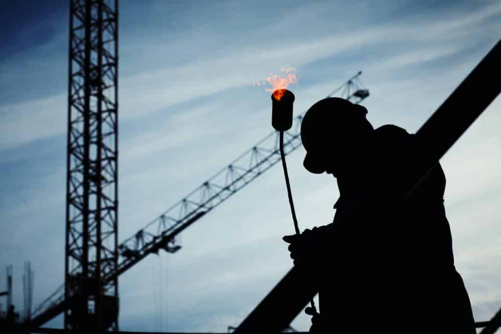 Silhouette of a man working hard at a construction site