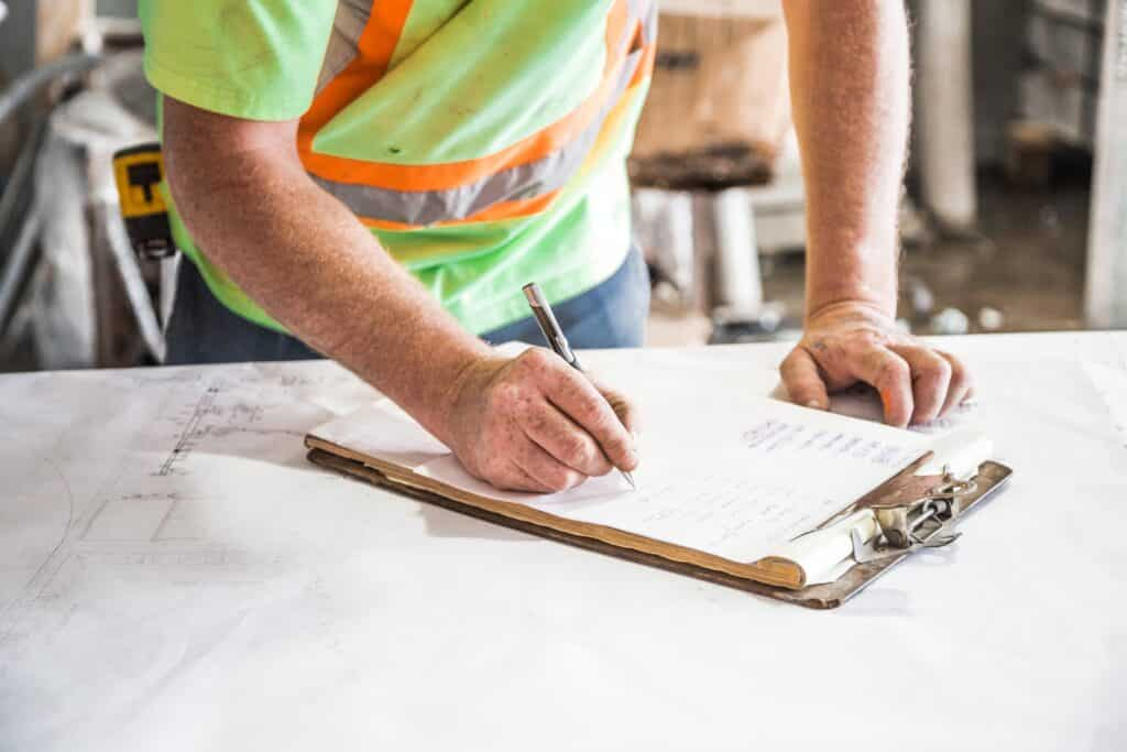 Construction worker writing down on paper after getting the job with his professional resume